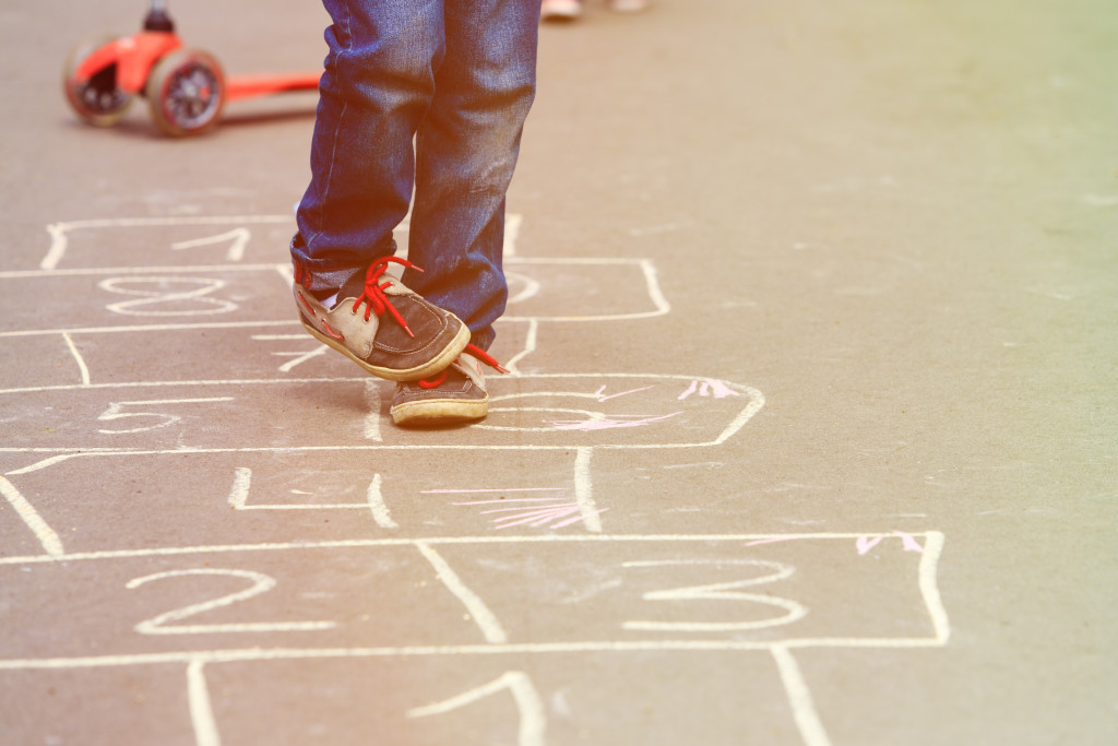 little boy playing hopscotch outdoors